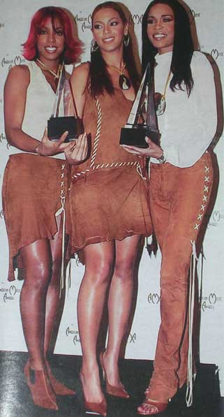 Dressed in matching brown suede, Destiny's Child show off their two American Music Awards for favourite pop album and favourite soul group.